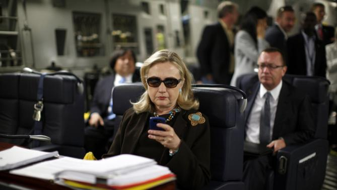 File photo of U.S. Secretary of State Hillary Clinton checking her PDA upon her departure in a military C-17 plane from Malta bound for Tripoli